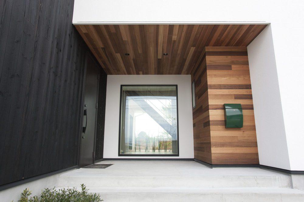 焼杉と白の塗り壁と木の板貼りを組みあわせた玄関