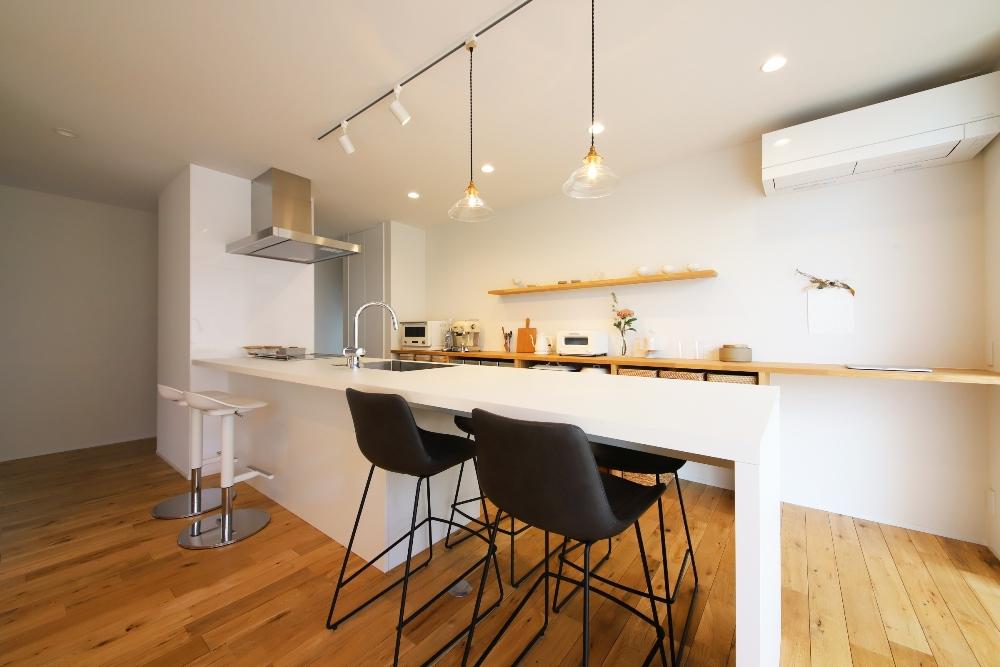 ダイニング照明が映える一体型の白いキッチン